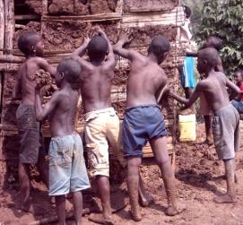 En RDC, des enfants Tapori aident à refaire la maison de leur ami Imani en 2006. Les maisons en terre sont vite abîmées lorsqu'il pleut et il faut les consolider régulièrement (ph. Tapori RDC).