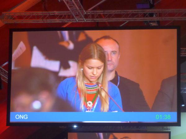 Une jeune femme d'une ONG représentant le groupe des populations autochtones s'exprime en plénière. Il a 8 groupes différents pour des milliers d'ONG et seule une personne par groupe peut s'exprimer.